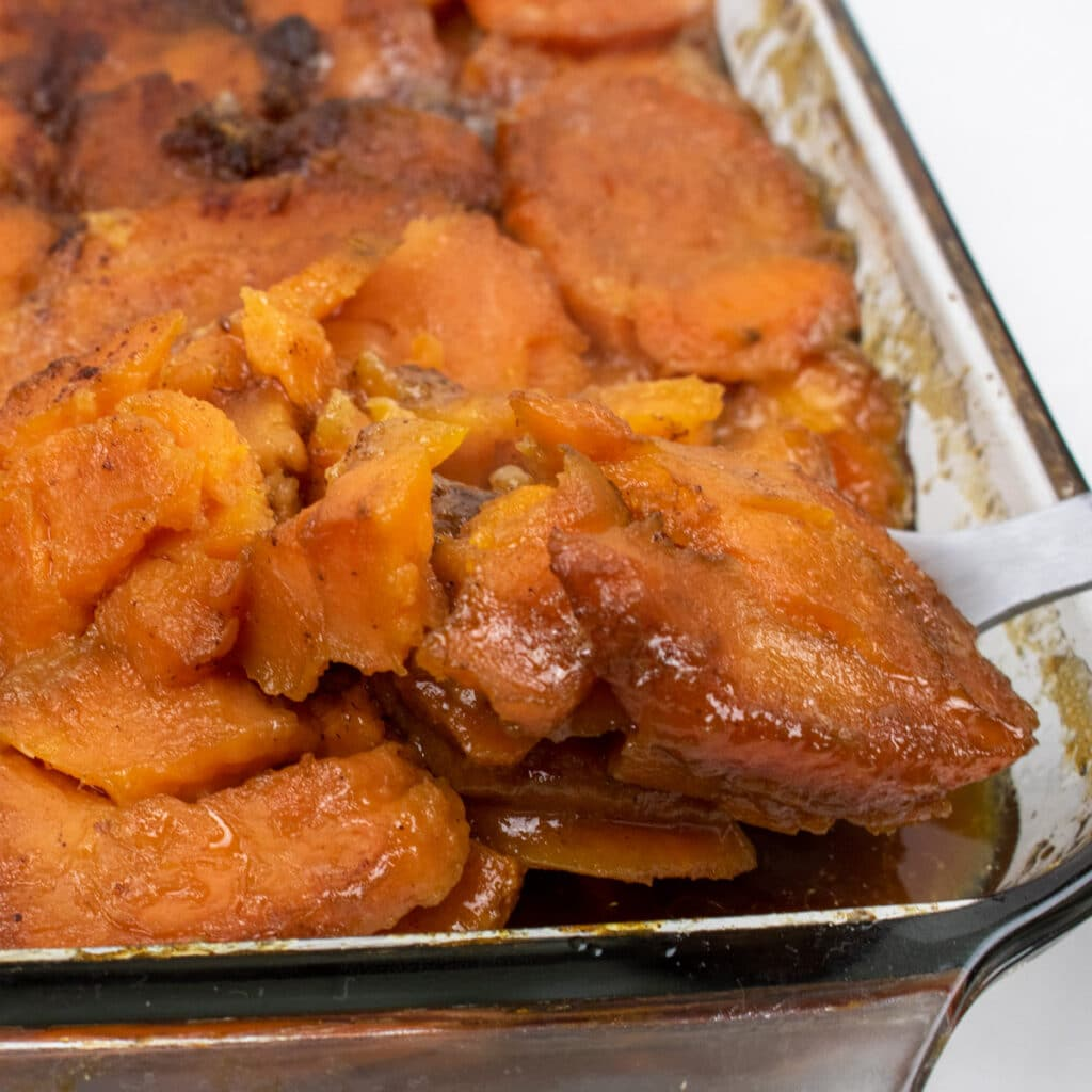 candied yams in a glass baking dish with a serving spoon inserted