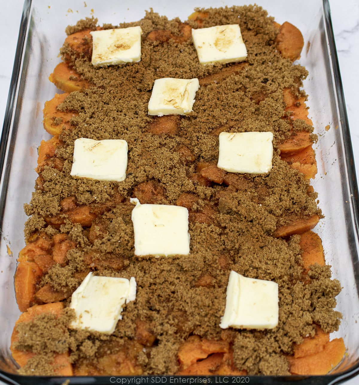 sliced sweet potato layer with brown sugar, cinnamon and butter in a baking dish