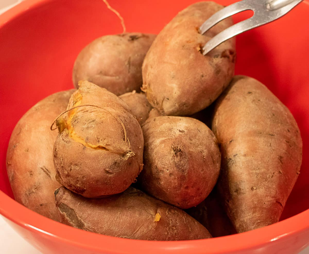 cooked sweet potatoes in a red bowl with a fork probe