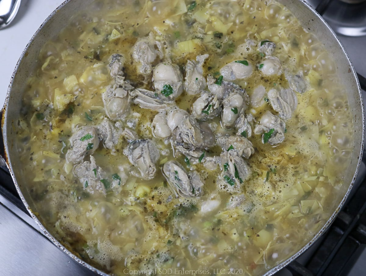 sauteed oysters added to stock and vegetables in a frying pan