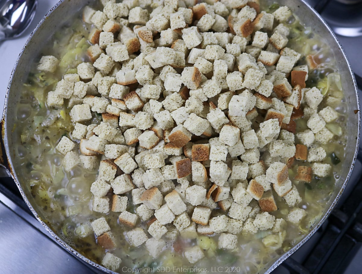 bread cubes added to a skillet with dressing ingredients in a frying pan