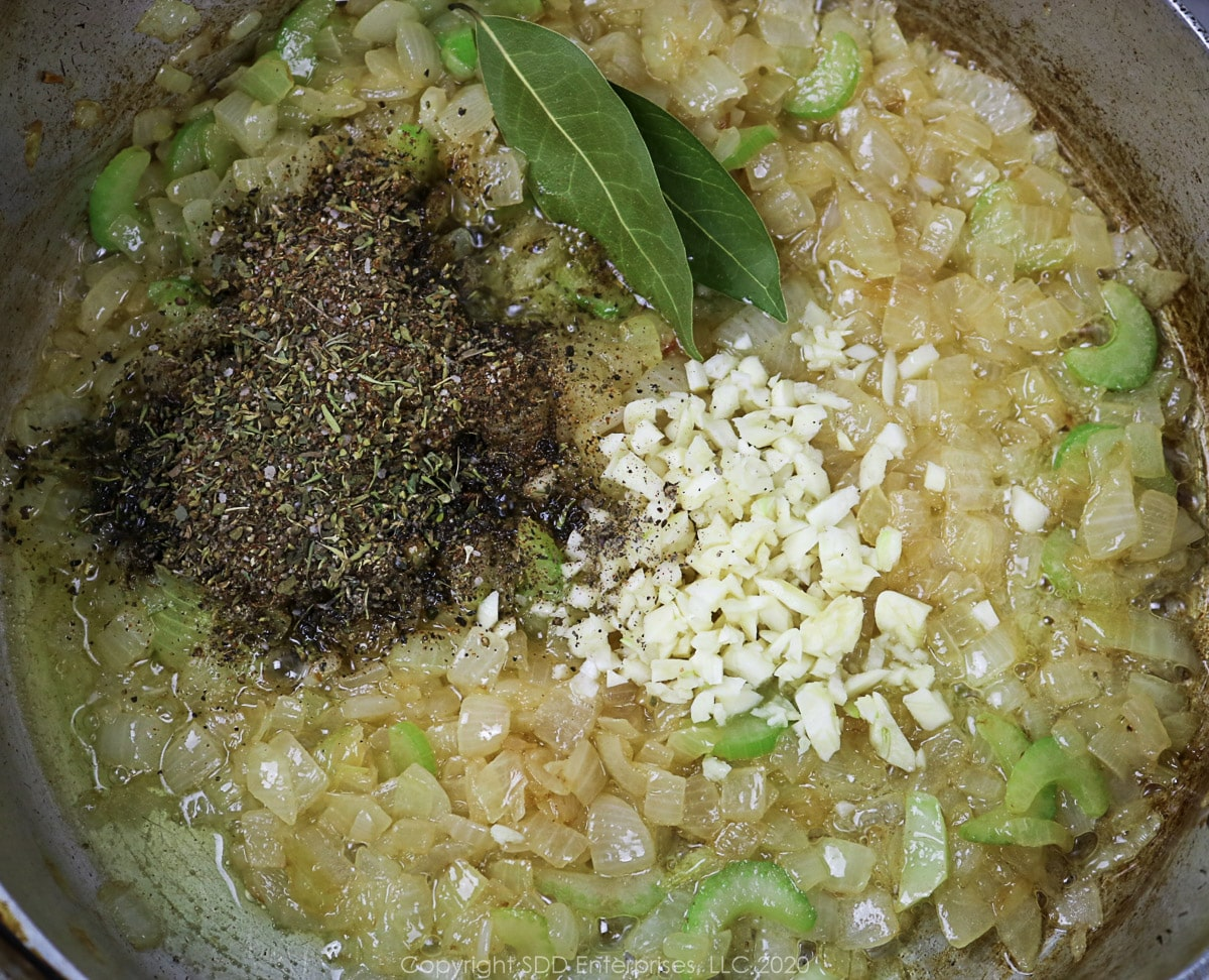 herbs and spices and garlic added to sautéing vegetables in a frying pan