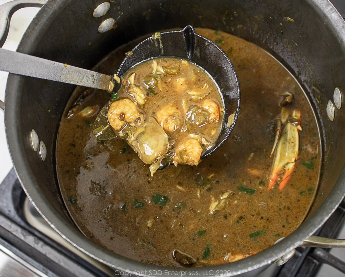 a ladle of seafood gumbo over a stockpot full of gumbo