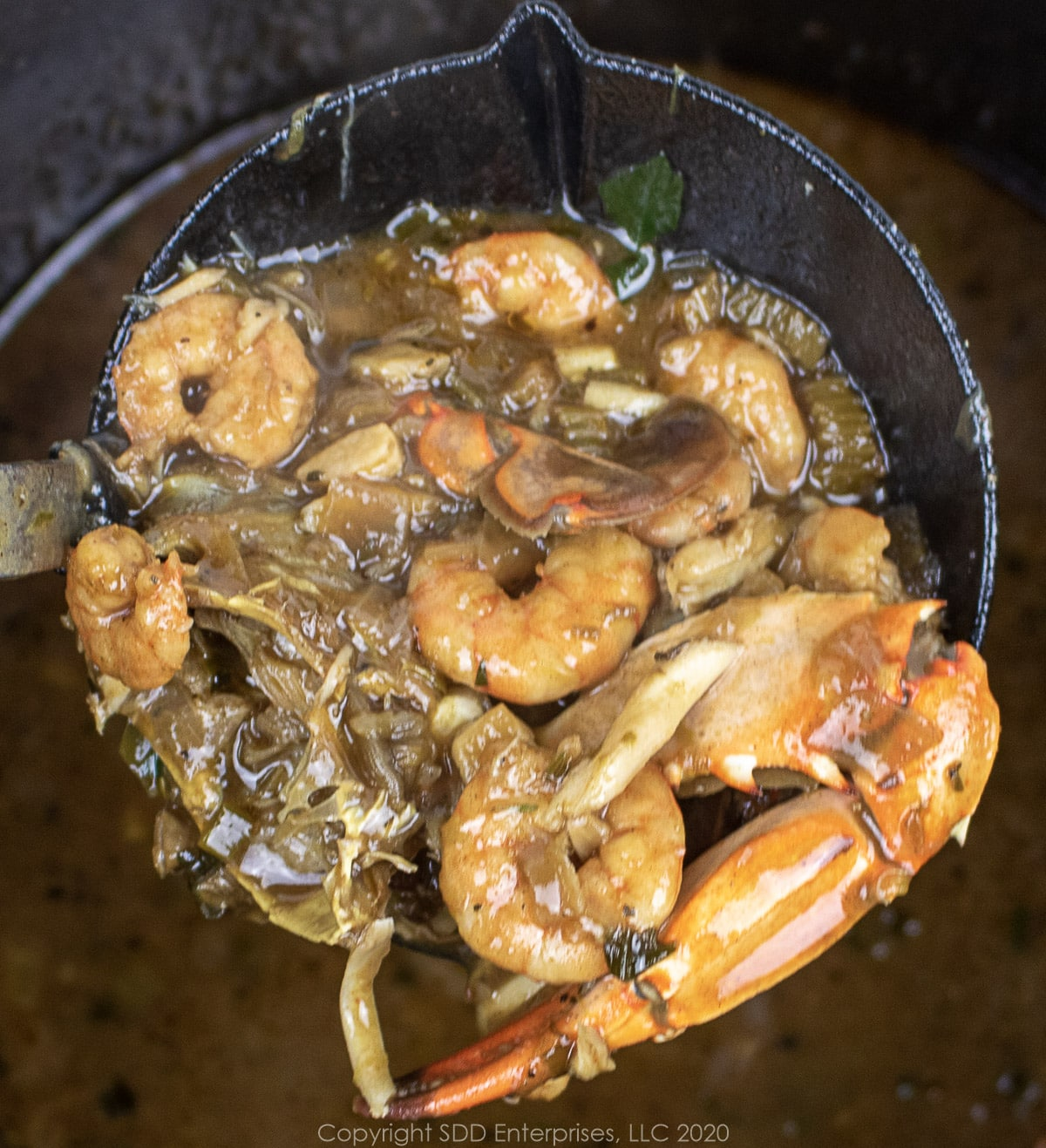 a ladle of seafood gumbo over stockpot