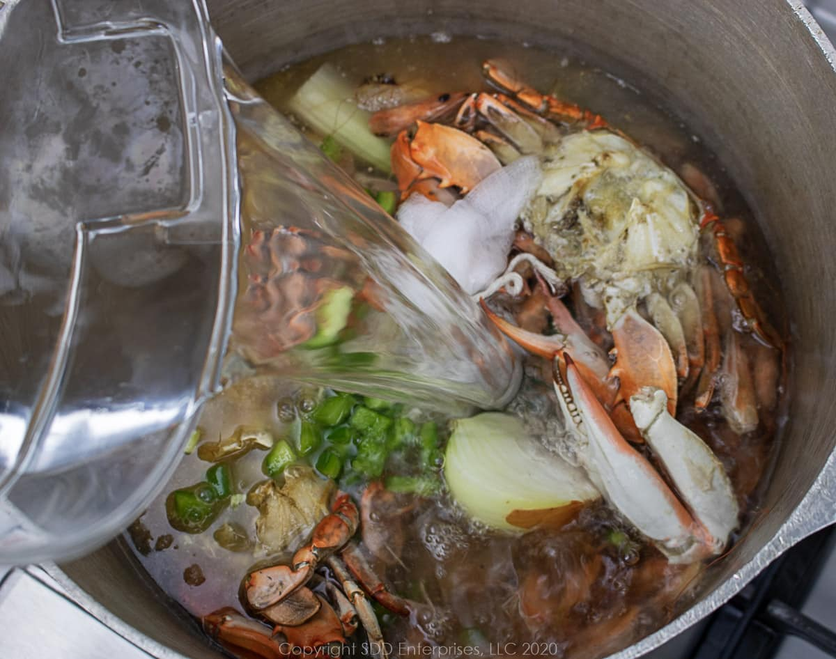 water being added to stockpot for seafood stock