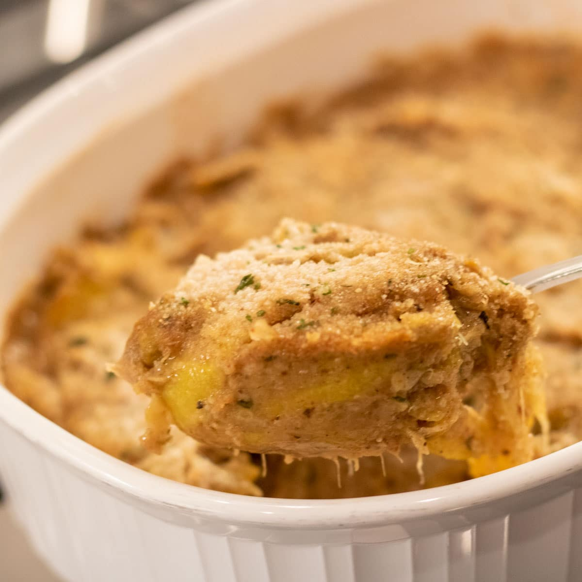 spoonful of yellow squash casserole in a white baking dish