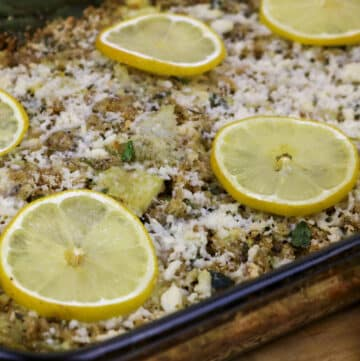 stuffed artichoke casserole topped with lemon slices in a baking dish
