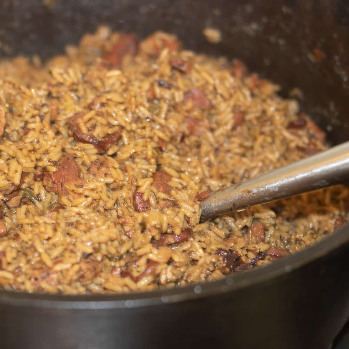 cajun jambalaya with sausage in a large cast iron pot with a serving ladle