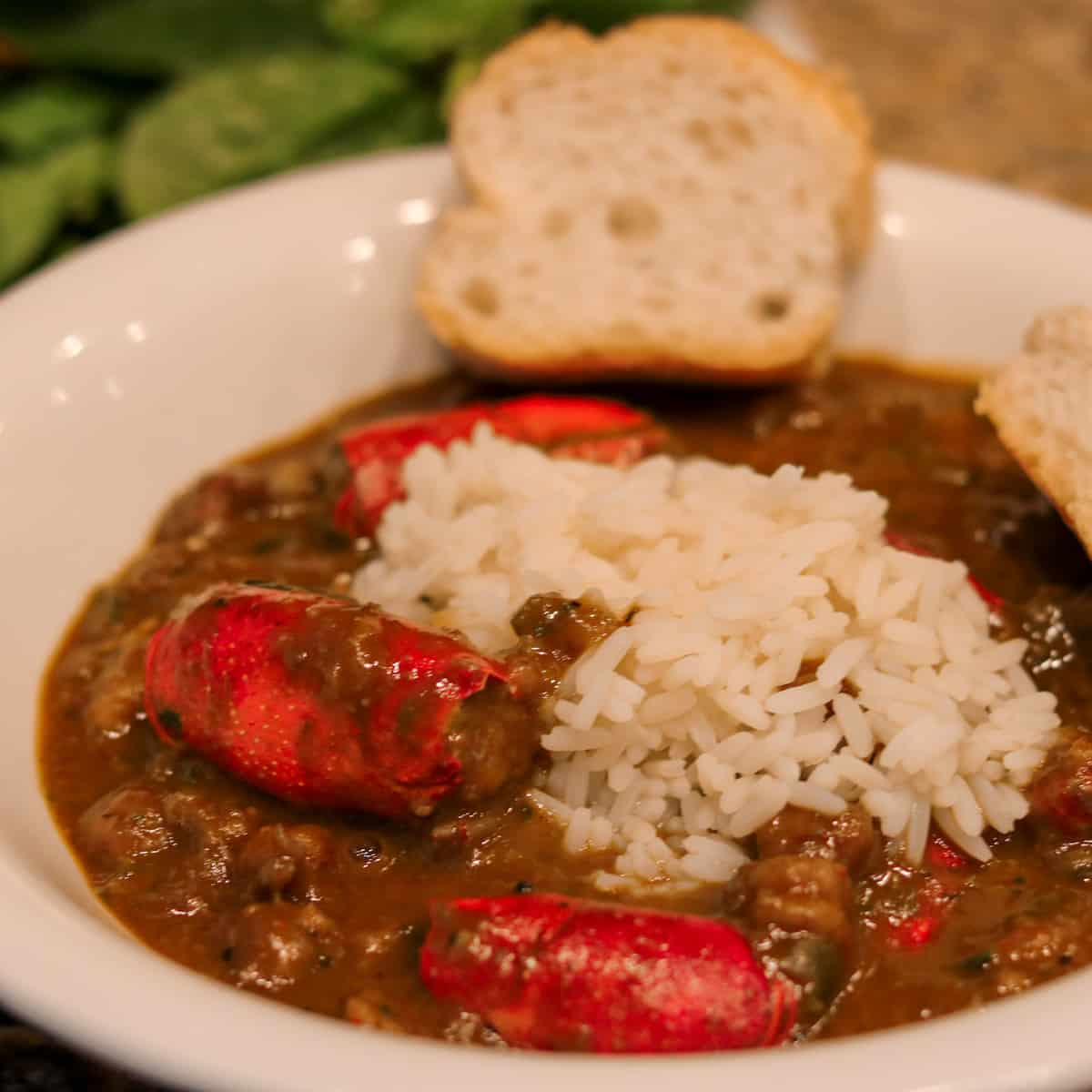 crawfish bisque with stuffed heads and rice in a white bowl with french bread and salad