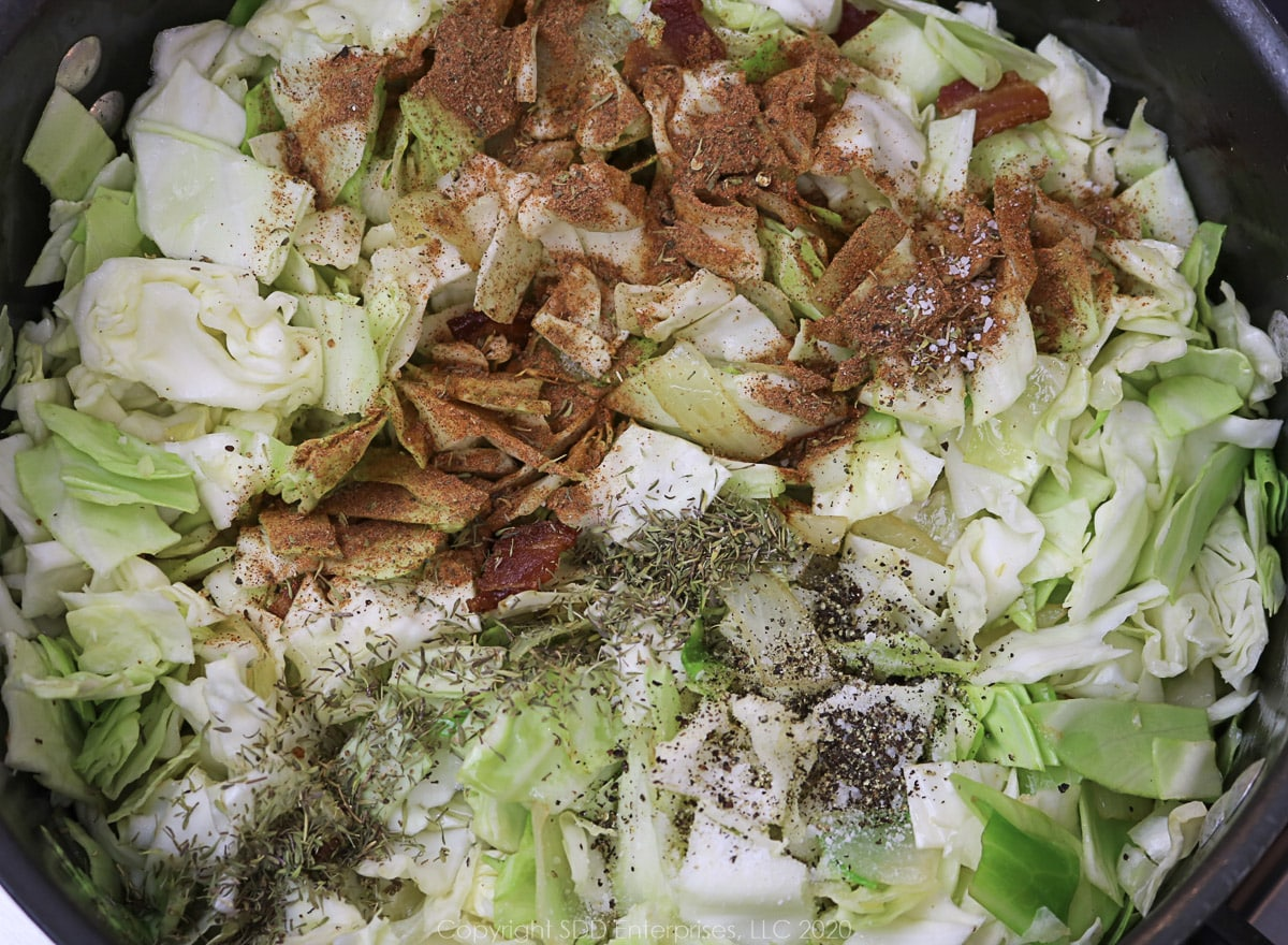seasonings added in with cabbage and onions in a dutch oven