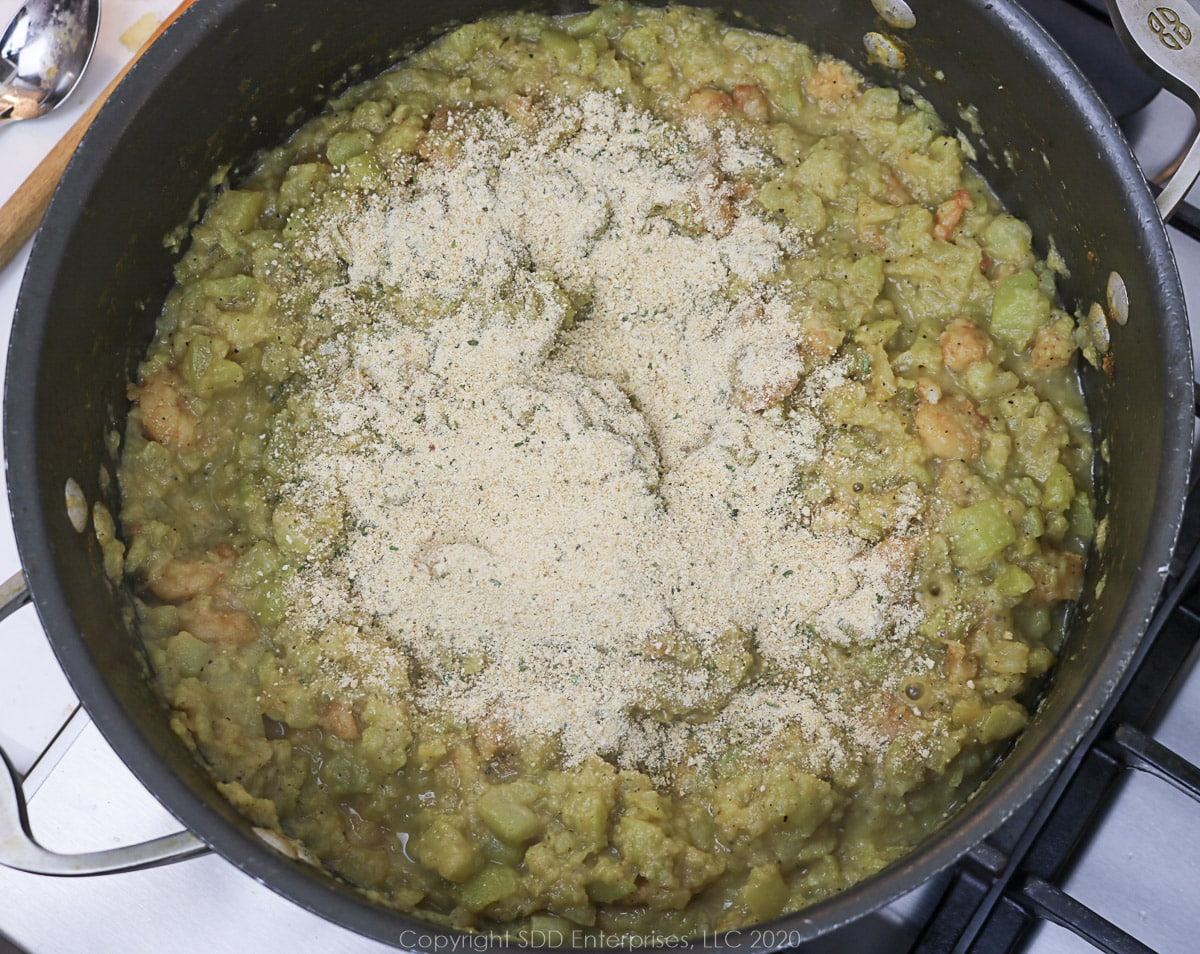 seasoned breadcrumbs added to mirliton mixture in a Dutch oven