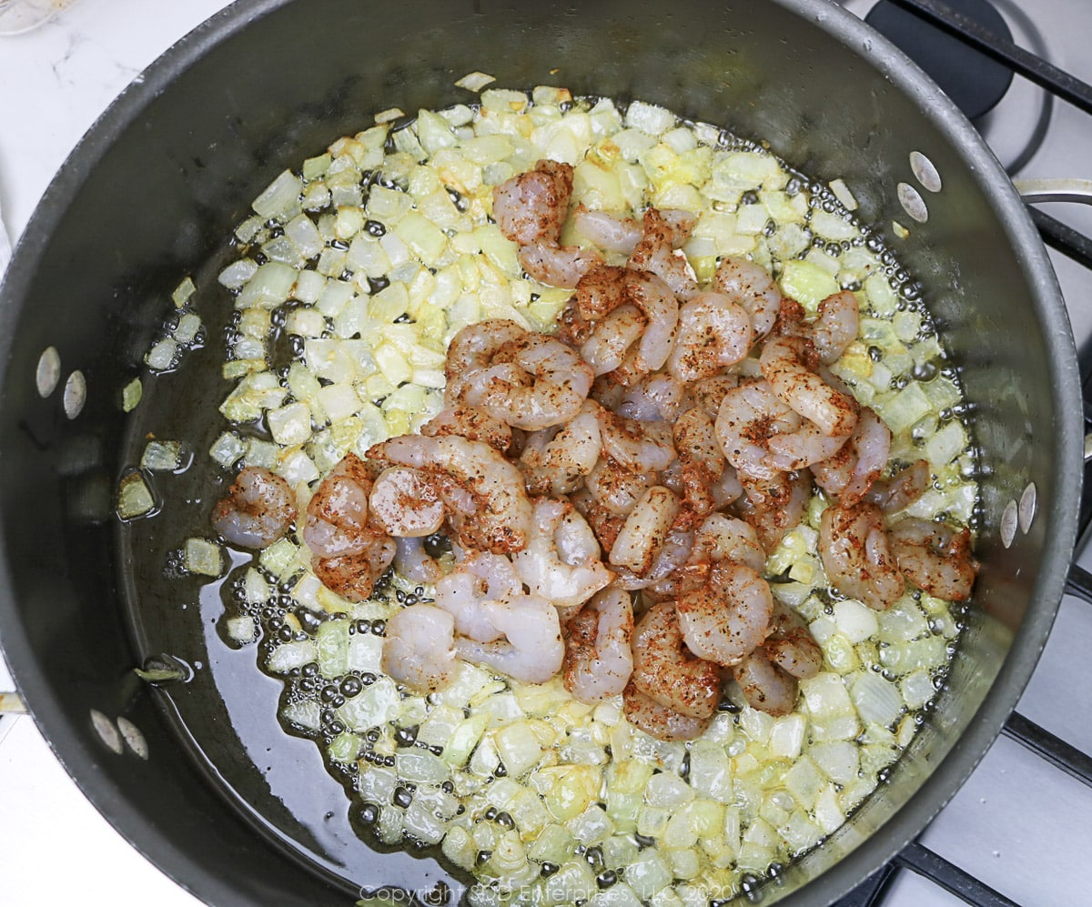 seasoned shrimp added to onions in a Dutch oven