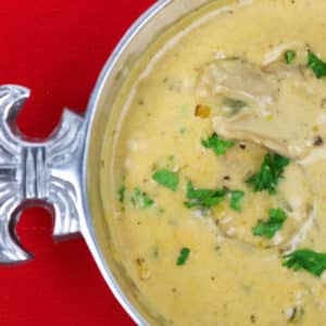 oyster soup in a silver bowl with fleur de lis on a red background