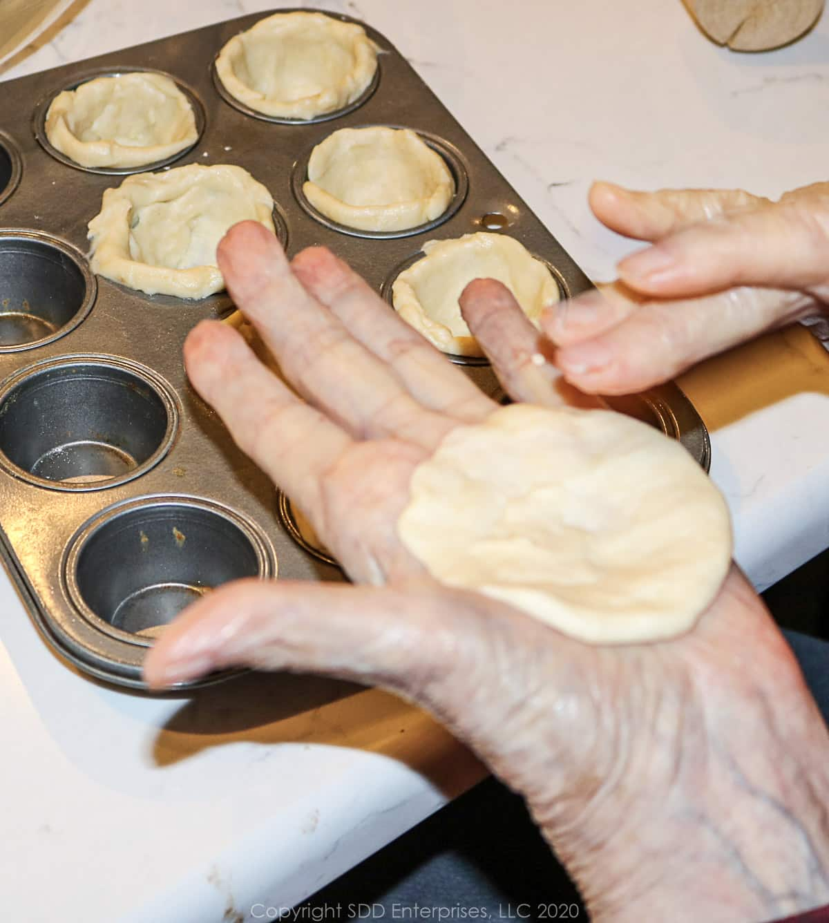 flattened dough going into a mini muffin tin