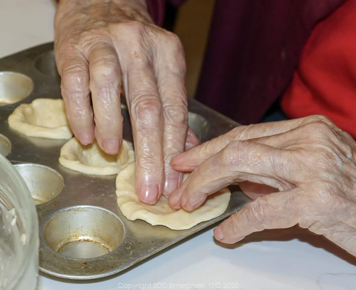 placing dough in mini muffin tins