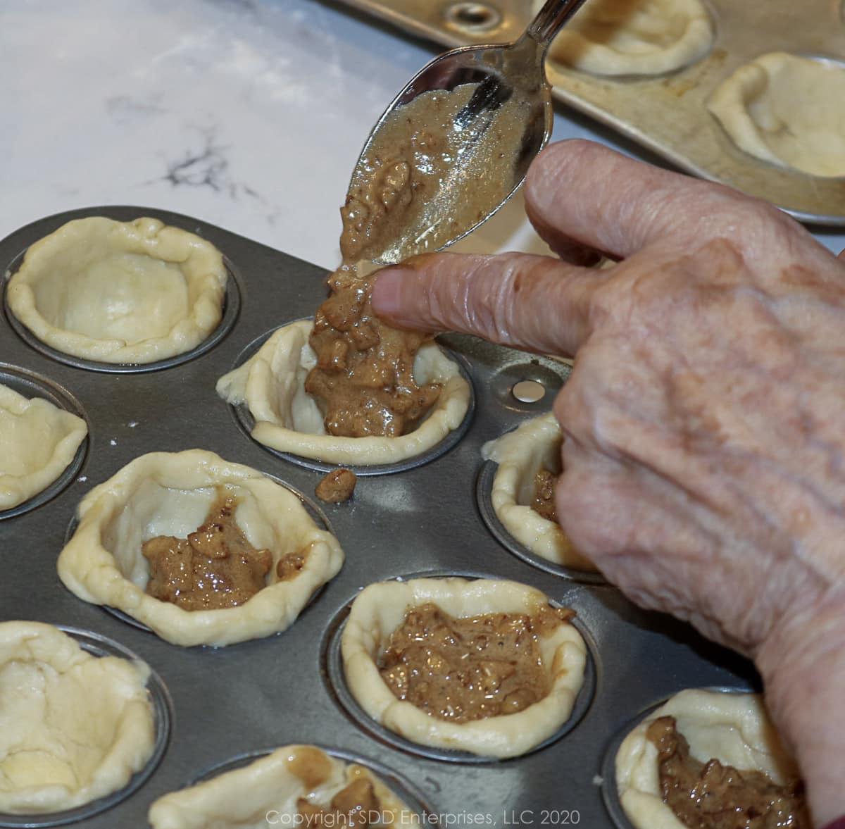 placing pecan filling in individual tart crusts