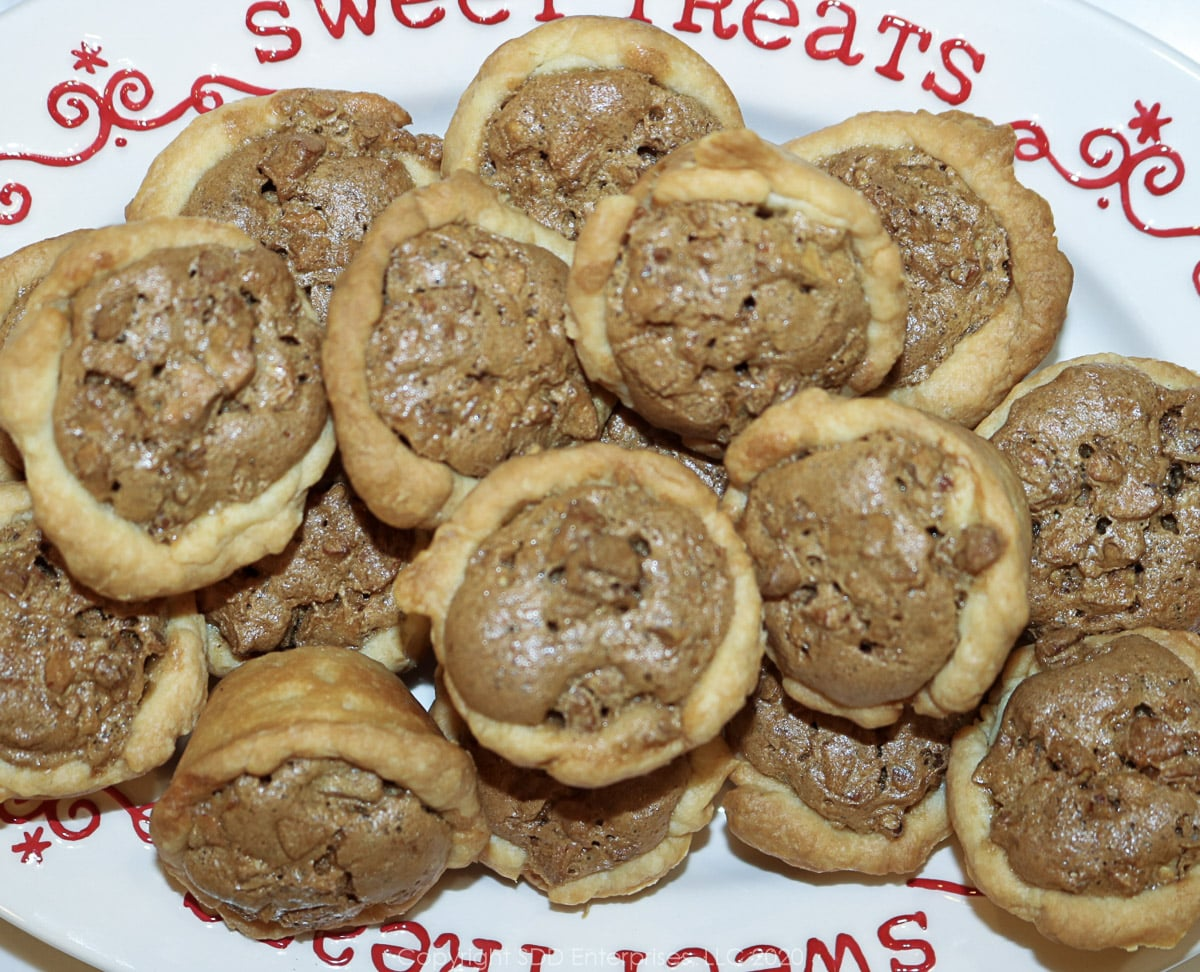 several pecan tarts on a white holiday dish