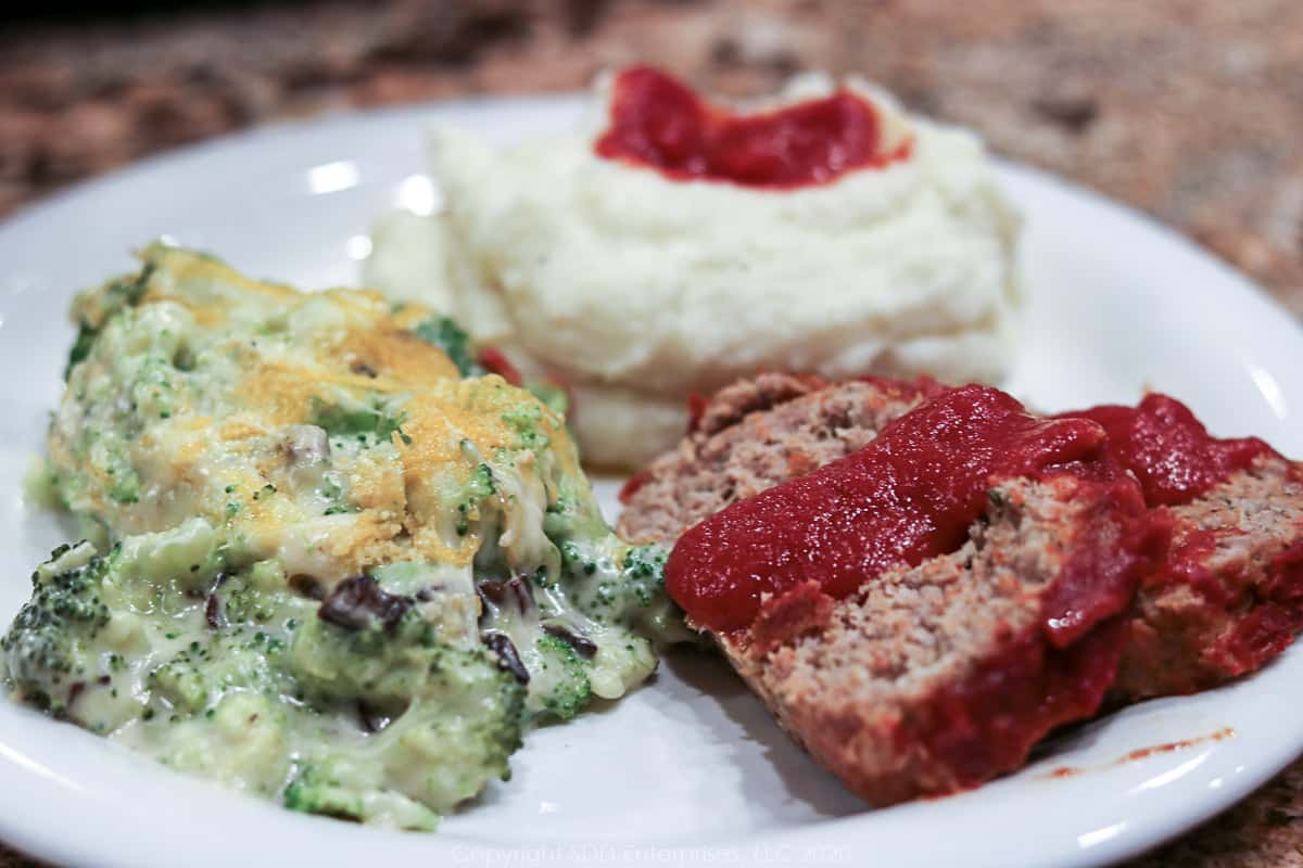 meatloaf with gravy on a plate with mash potatoes and broccoli casserole