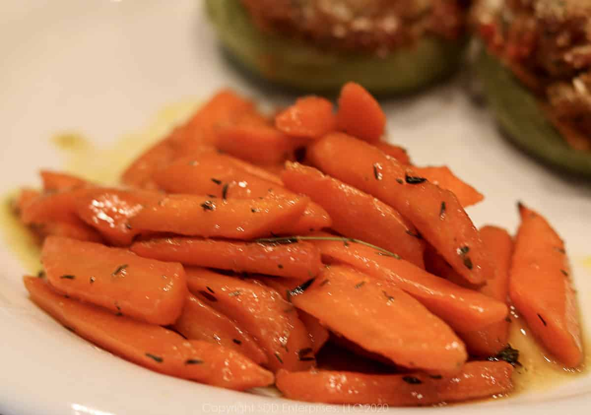 roasted carrots with cane syrup on a plate with stuffed mirliton