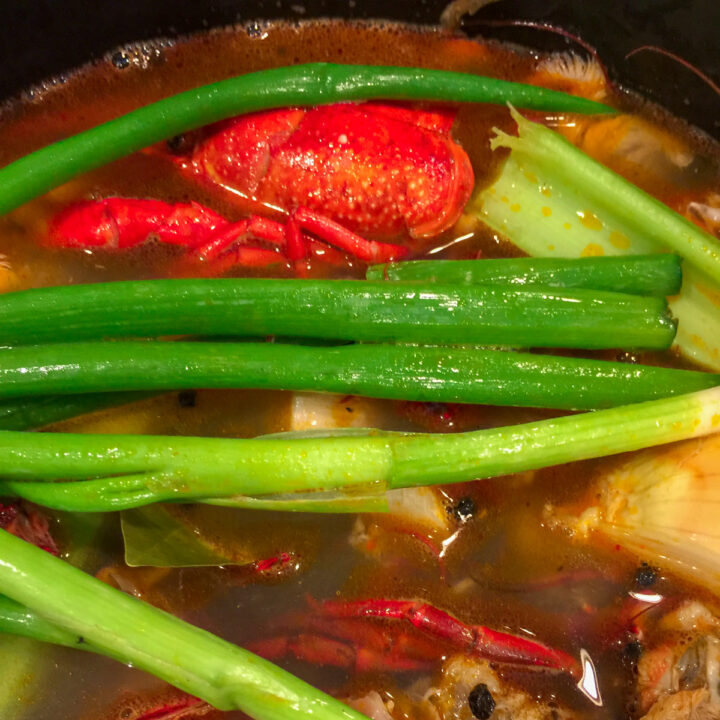 crawfish shells, green onions, yellow onions and celery with water in a stock pot