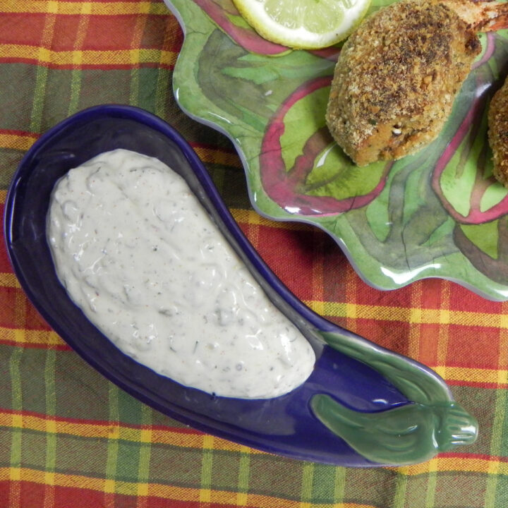 creole tartar sauce in a snall serving bowl with stuffed shrimp on the side