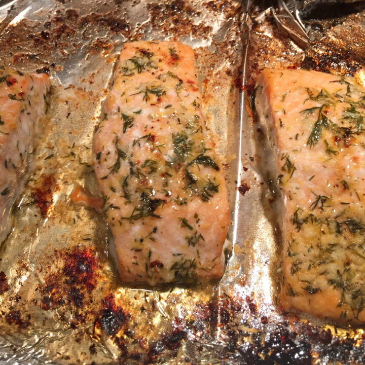 baked salmon fillets with herb butter on a baking sheet