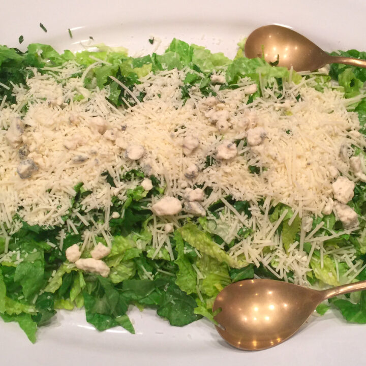 sensation salad with Romano cheese on top and serving spoons on a platter