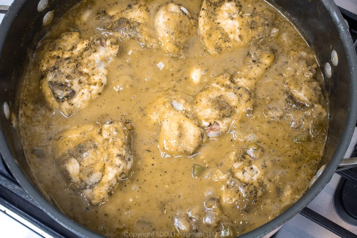 chicken simmering in gravy in a Dutch oven