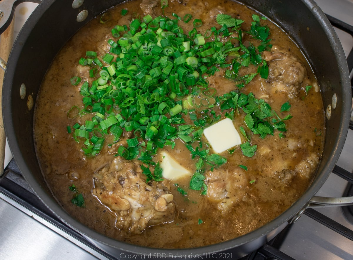 green onions, parsley and butter added to smothered chicken in a Dutch oven