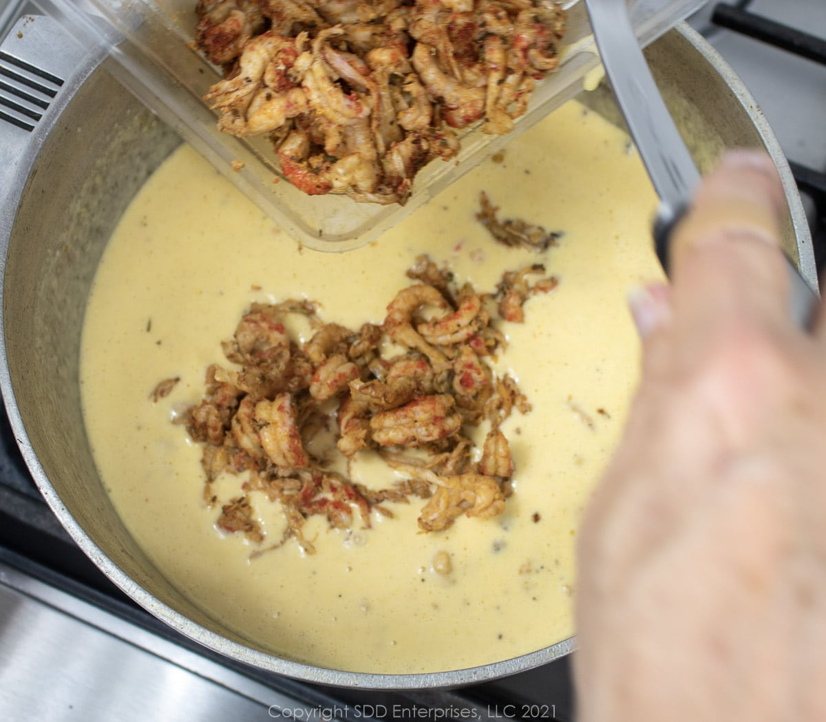 seasoned crawfish tails added to cheese sauce in a Dutch oven