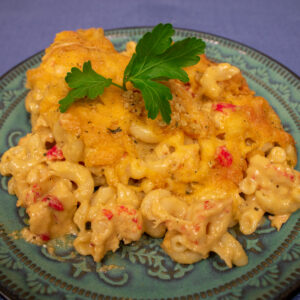 crawfish mac and cheese on a green plate with parsley garnish