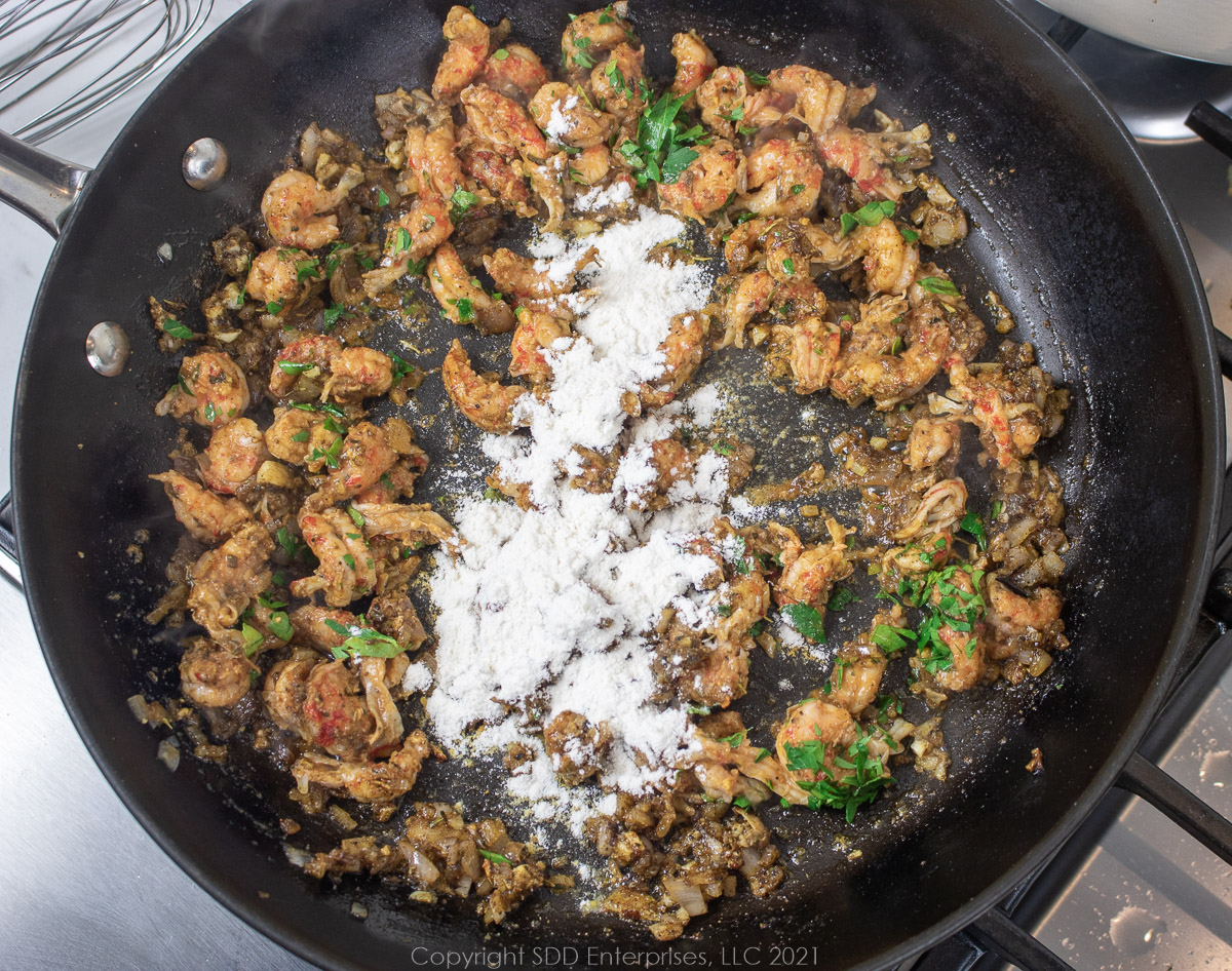 crawfish tails and AP flour added to sautéing onions and aromatics in a frying pan