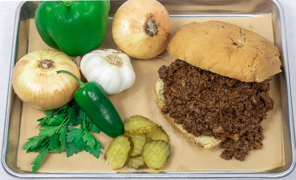Sloppy Joes on a bun with onions, peppers, garlic, pickles and parsley garnish