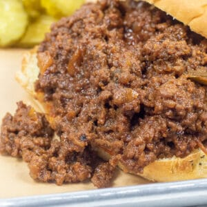sloppy joes om and onion roll with pickles on the side