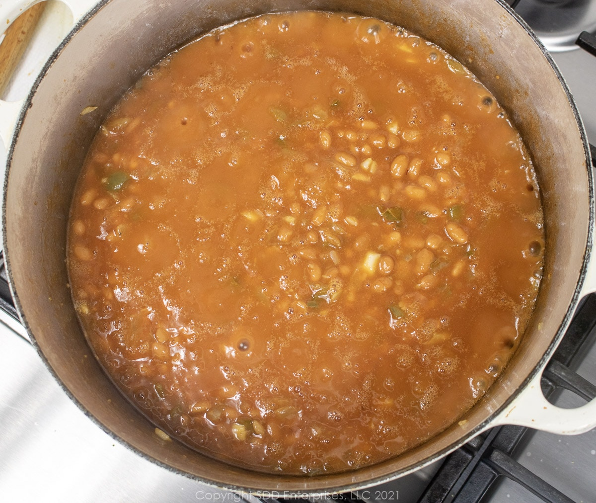 canned beans and vegetables simmering in a Dutch oven