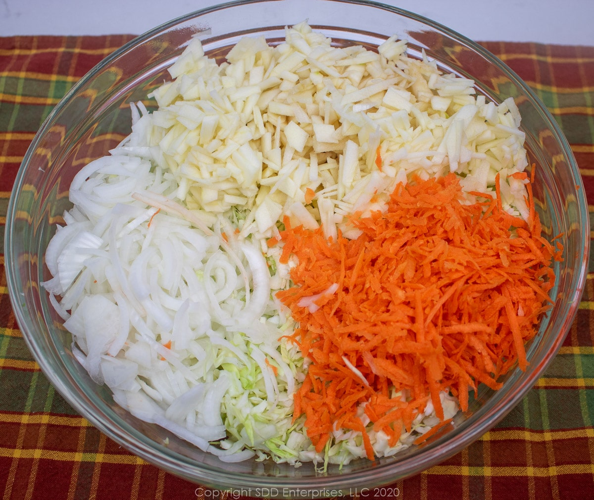 shredded cabbage, onions, carrots and apples in a glass bowl