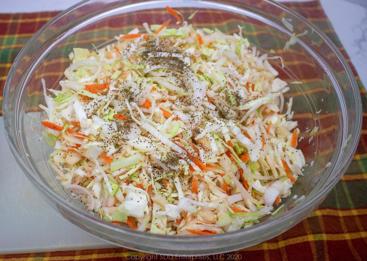 shredded cabbage mixed with apples, onions, carrots and celery seeds