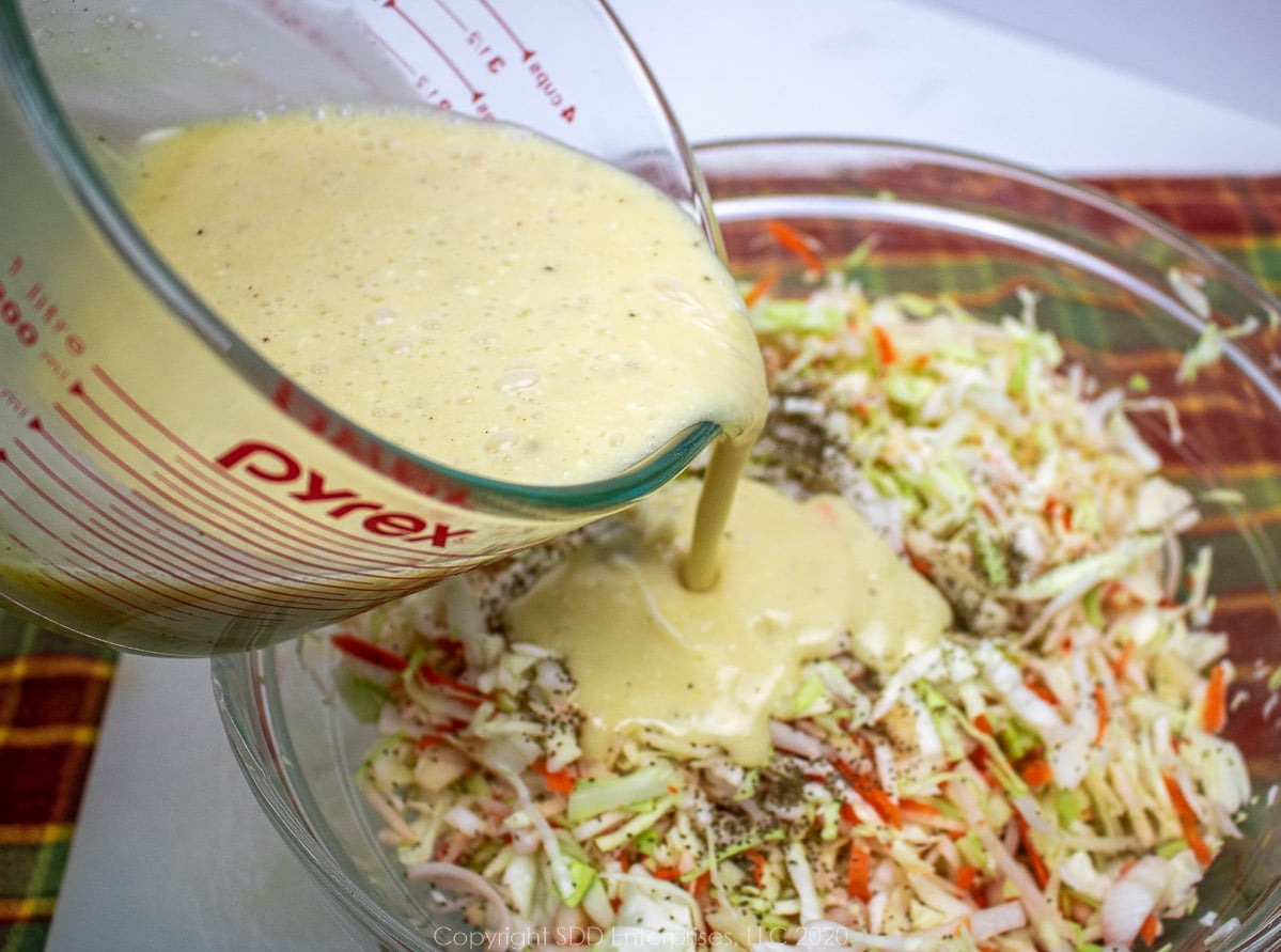 dressing being poured onto chopped cabbage, onions, apples and carrots