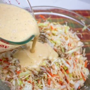creamy dressing being poured on shredded cabbage, apples, carrots and onions in a glass bowl