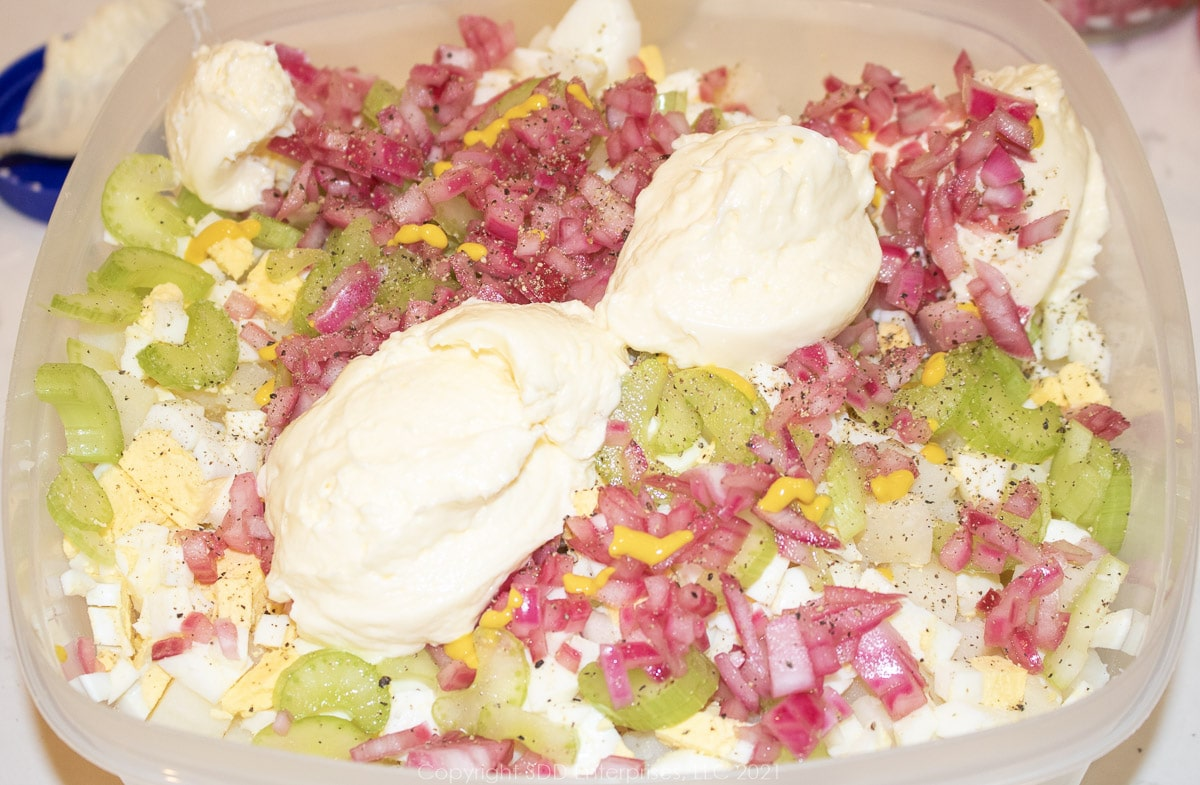 mayonnaise and yellow mustard added to boiled potatoes and eggs in a mixing bowl