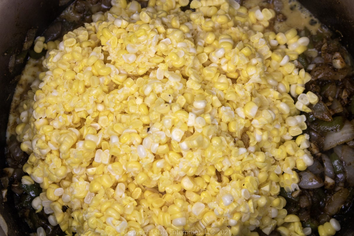 fresh corn with frying vegetables in a Dutch oven