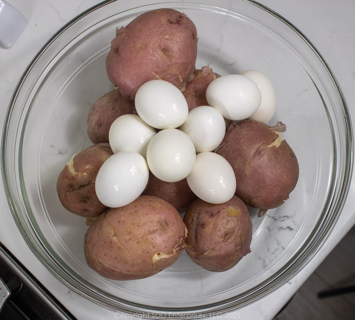 boiled eggs and potatoes in a glass bowl