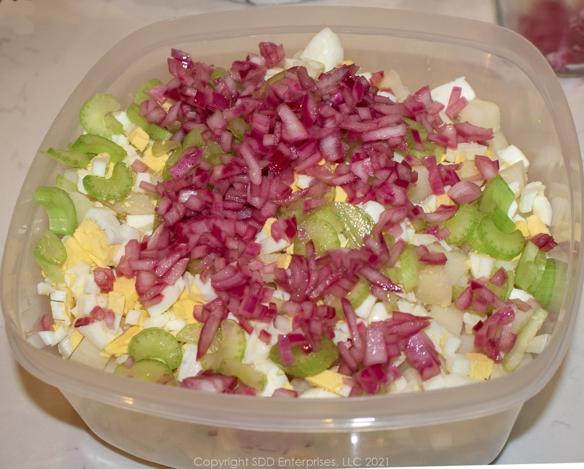marinated onions and chopped celery added to boiled eggs and potatoes in a mixing bowl