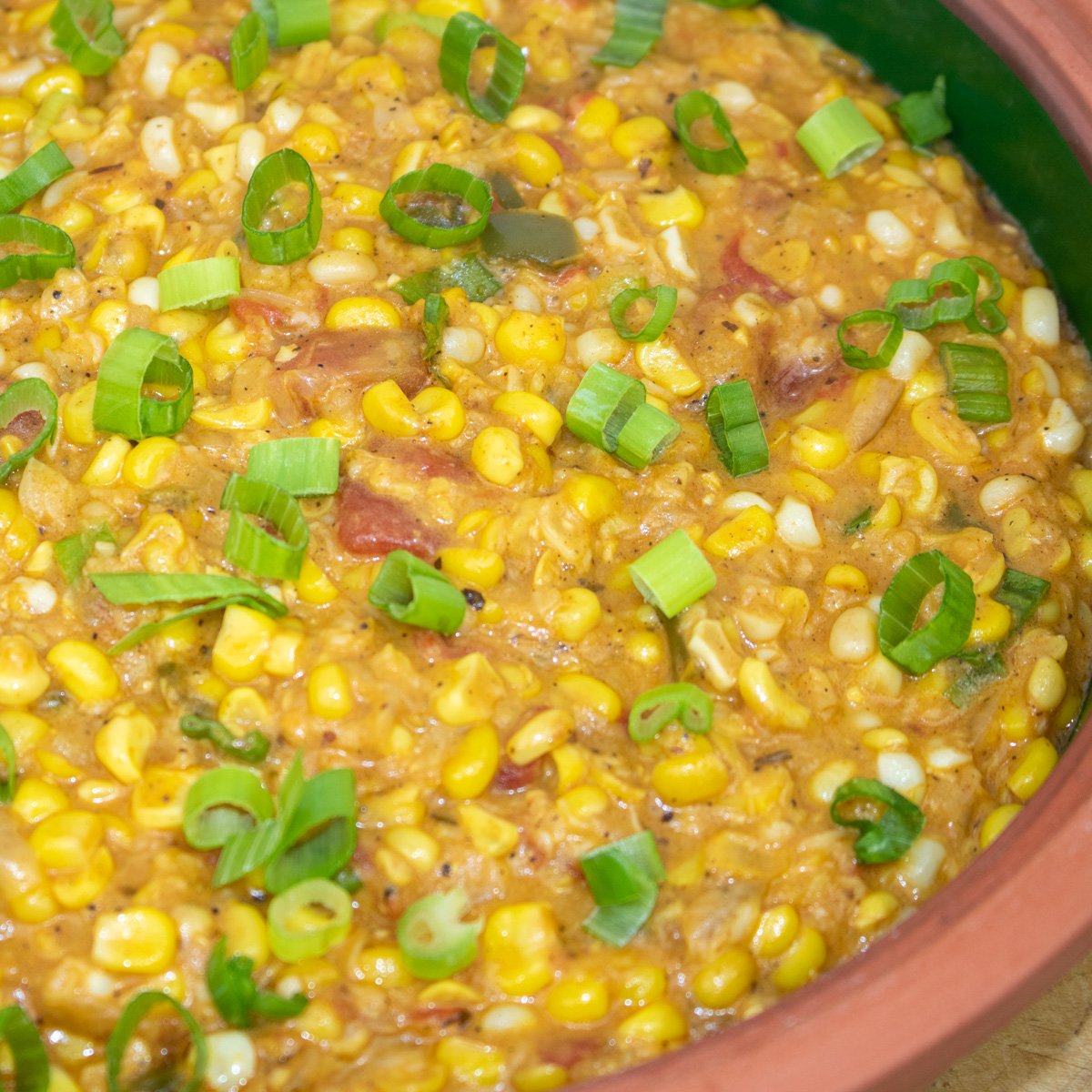 corn maque choux with green onion garnish in a brown bowl