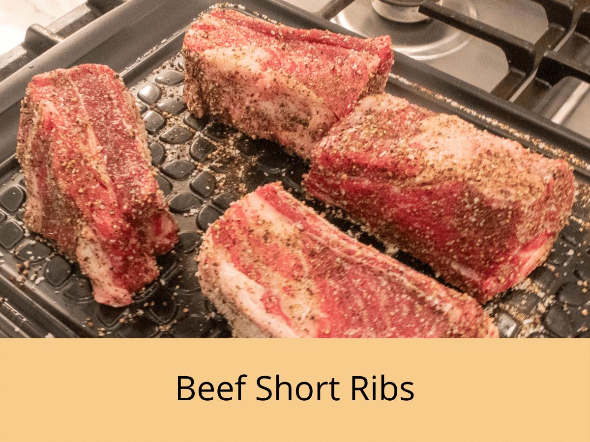 seasned beef short ribs on a black platte