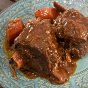 braised beef short ribs with gravy and carrots on a blue-green plate