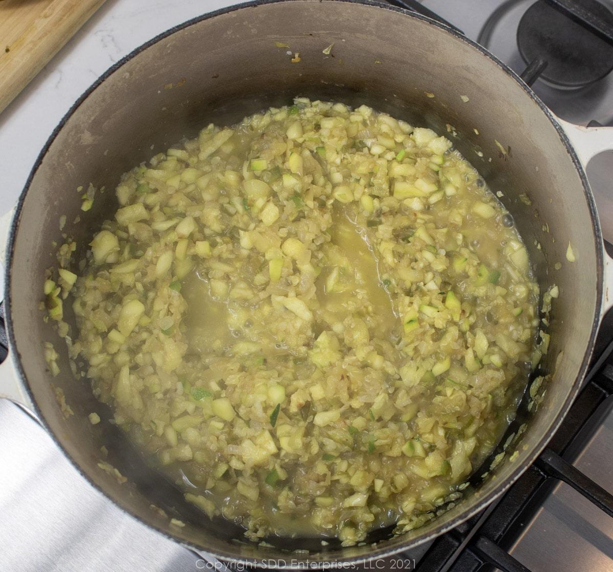 chopped zucchini simmering in a Dutch oven