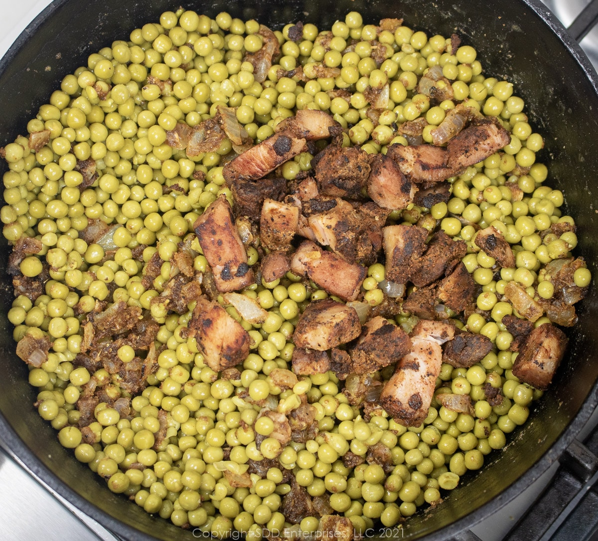 sweet peas and seasoning meat added to vegetables and roux in a Dutch oven