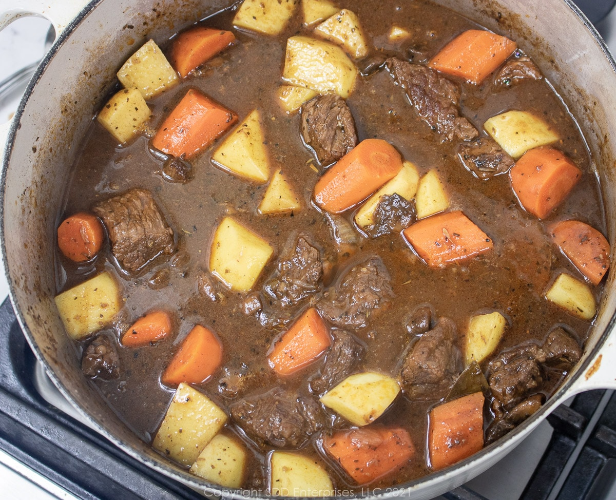 potatoes added to carrots and beef in a Dutch oven